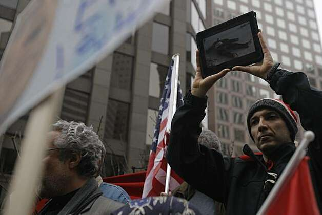 Hussein Moustafa holds up an iPad displaying pictures from protests in Egypt during a rally in San Francisco in support of the Egyptian people and against Hosni Mubarak and the Egyptian government Saturday. Photo: Thomas Levinson, The Chronicle