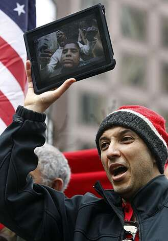 Hussein Moustafa displays photos from the riots in Egypt on his iPad during a rally at Market and Montgomery streets in San Francisco on Saturday supporting the uprising against President Hosni Mubarak in Egypt. Several hundred protesters gathered to hear speeches and later marched to United Nations Plaza. Photo: Paul Chinn, The Chronicle