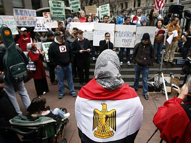 Wrapped in the national flag of Egypt, Laila Barakat listens joins several hundred demonstrators during a rally at Market and Montgomery streets in San Francisco on Saturday supporting the uprising against President Hosni Mubarak in Egypt. Photo: Paul Chinn, The Chronicle