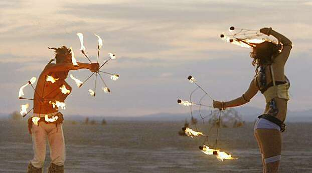 Fire dancers perform at sunrise in front of the temple at the Burning Man festival in Black Rock City., NV on September 4, 2009. Photo: Frederic Larson, The Chronicle