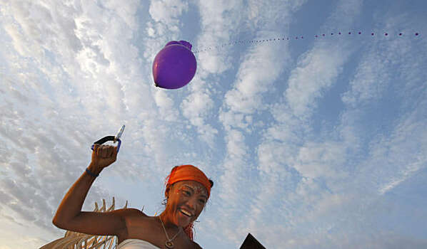 A woman carries a long string of balloons hundreds of feet above the playa at the Burning Man festival in Black Rock City., NV on September 4, 2009. Photo: Frederic Larson, The Chronicle