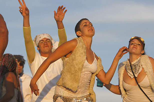 A group of revelers dance to the sunrise over the playa at Burning Man at Black Rock, NV., on September 3, 2009.