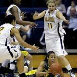 Oregon's Tamika Nurse passes the ball from the floor after losing her footing during the first half of play. The Cal Womens' Basketball team played the Oregon Ducks at Haas Pavilion in Berkeley on Thursday, January 10, 2008.