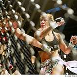 Cristiane Cyborg from Curitiba Brazil right, lands a right hand punch on the face of Shayna Baszler from Sioux Falls SD in the second round of their cage-fight at the Stockton Arena Saturday night July 25, 2008. Cyborg defeated Baszler in front of thousand's of fans.
