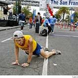 Adam Coleman of Clayton, Calif. falls to the ground with a leg cramp after crossing the finish line in the San Francisco Marathon, Sunday, Aug. 3, 2008, in  San Francisco, Calif.