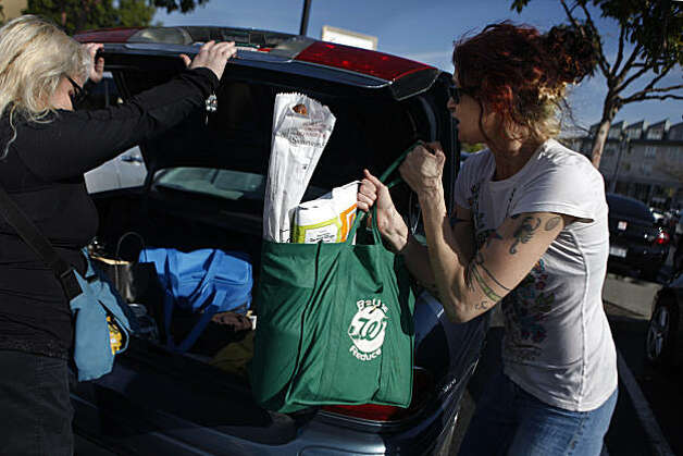 Yvette Pouyadou (right) of San Francisco loads her groceries in a Walgreen's reusable bag into a car as Michele Doyle (left) of Chico holds open the trunk door on Monday, January 24, 2011 in San Francisco, Calif. Photo: Lea Suzuki, The Chronicle
