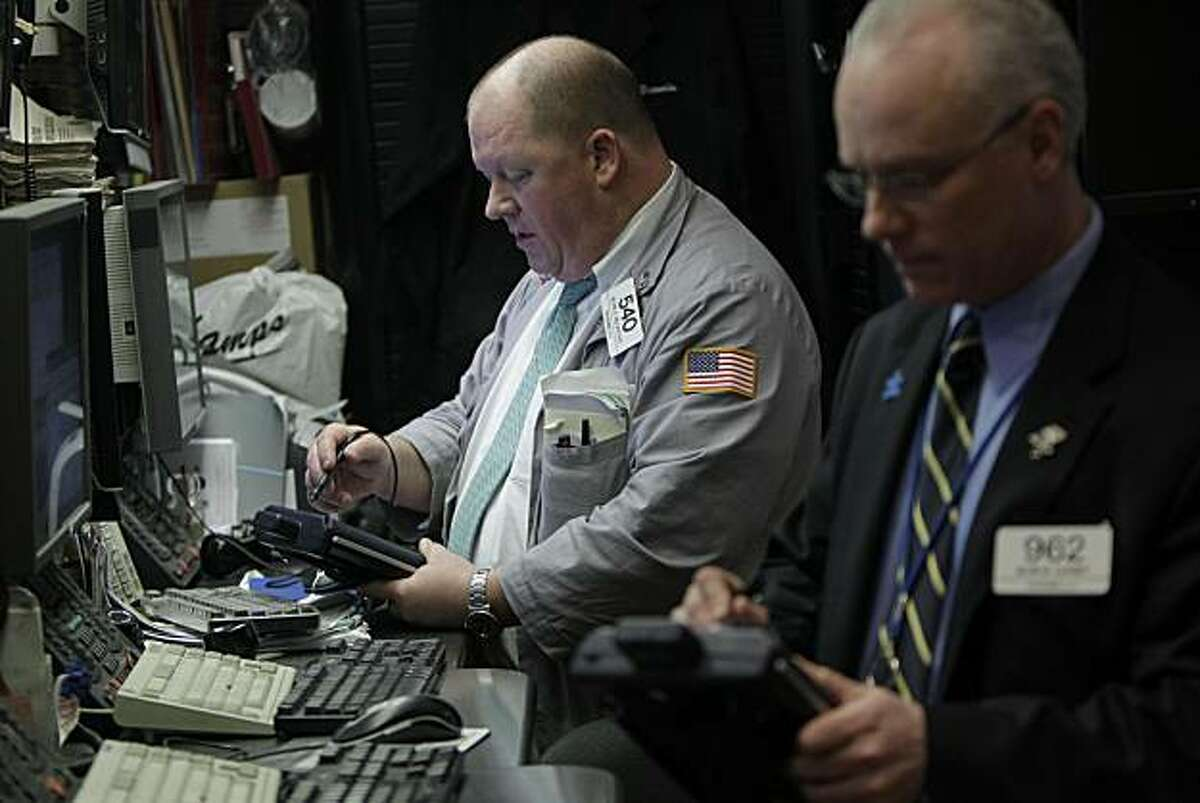 Traders work on the floor at the New York Stock Exchange in New York, Monday, Jan. 24, 2011. The Dow Jones industrial average closed within 20 points of 12,000 Monday, its highest point since June 2008.