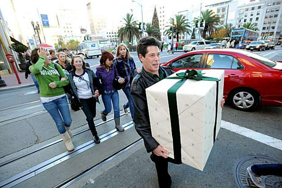 Stewart Selvick leaves Union Square carrying a gift-wrapped 7-piece All-Clad cookware set on Friday, Dec. 19, 2008, in San Francisco. Photo: Noah Berger, Special To The Chronicle