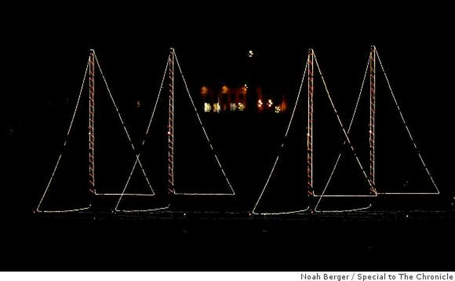 A decorated sailboat, seen in a multiple exposure image, passes Alcatraz during an annual holiday parade on Friday, Dec. 19, 2008, in the San Francisco Bay. Photo: Noah Berger, Special To The Chronicle