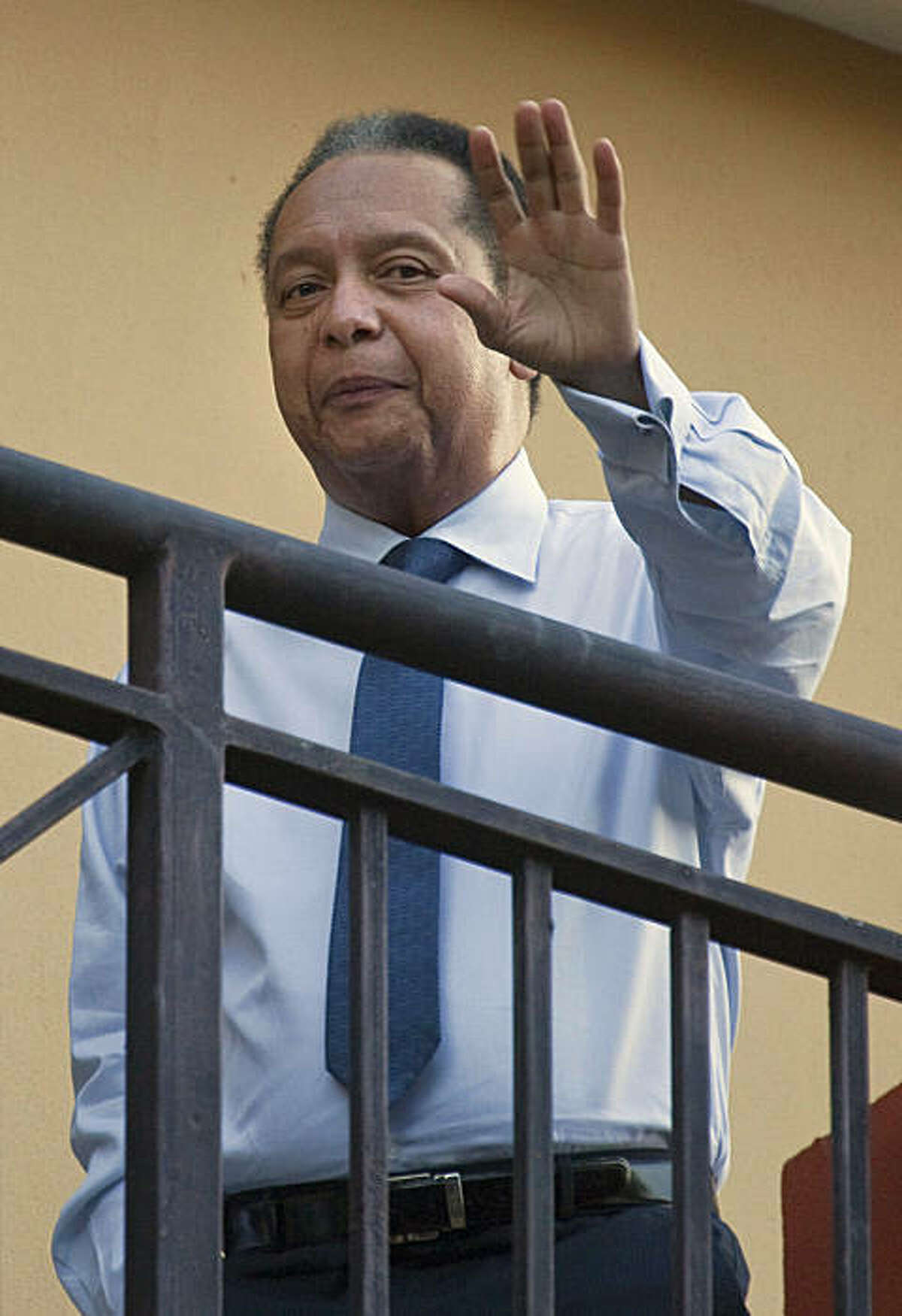 """Haiti's former dictator Jean-Claude """"Baby Doc"""" Duvalier waves to the press from a hotel balcony in Port-au-Prince, Haiti, Monday Jan. 17, 2011. Duvalier ensconced himself Monday in a high-end hotel following his surprise return to a country deep in crisis, leaving many to wonder if the once-feared strongman will complicate a political stalemate or prompt renewed conflict."""