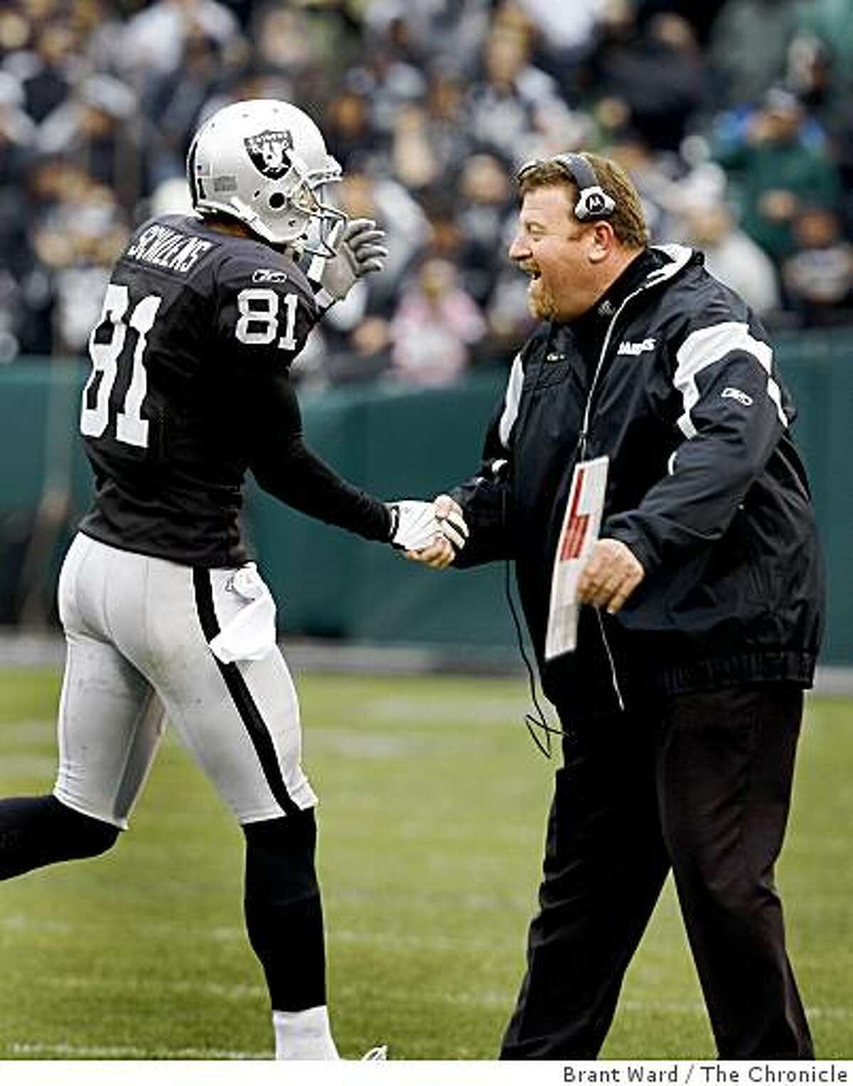 Raiders head coach Tom Cable congratulates Chaz Schilens (81) after his first quarter TD.