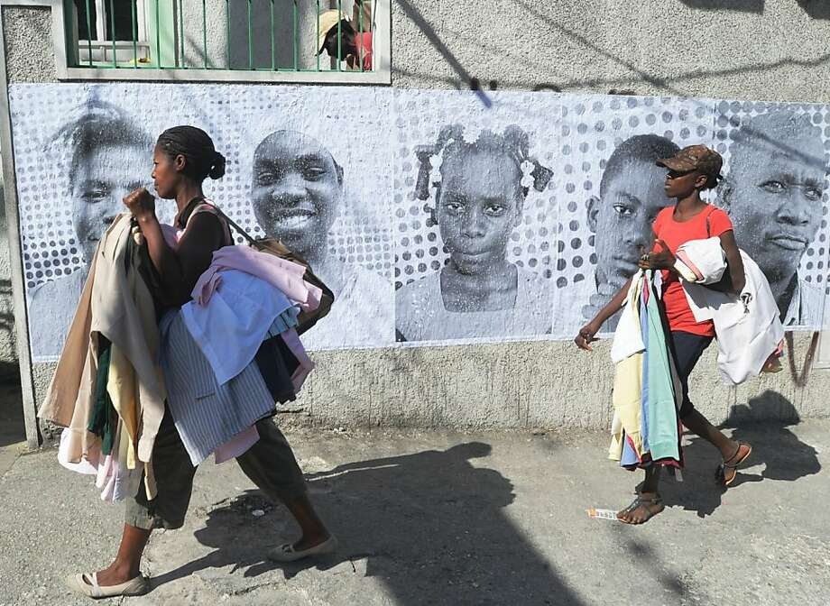 Woman walk by posters of victims of the January 12, 2011 earthquake on January 10, 2012 in Petion-ville , a suburb of Port-au-Prince. UN agencies said Tuesday that Haitians face many challenges on the second anniversary of the earthquake that killed more than 200,000 of their people, but those living in camps have dropped dramatically. AFP PHOTO Thony BELIZAIRE (Photo credit should read THONY BELIZAIRE/AFP/Getty Images) Photo: Thony Belizaire, AFP/Getty Images