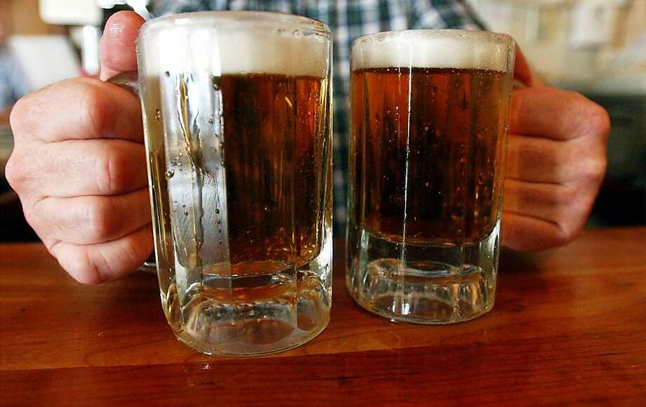 A bartender serves two mugs of beer at a tavern in Montpelier, Vt. Photo: Toby Talbot, Associated Press
