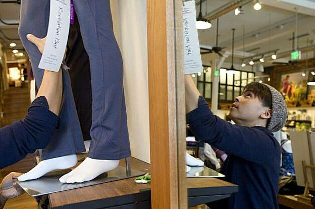 Kevin Vu arranges mannequins displaying pants at the new Athleta store on Fillmore Street in San Francisco, Calif., on Wednesday, January 12, 2011.  The company, owned by Gap, is trying to transition from a former e-commerce brand into a brick and mortar store. Photo: Laura Morton, Special To The Chronicle