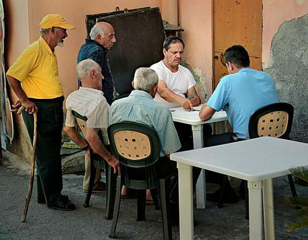 Men playing Scopa in Forza D'Agro, Sicily. Photo: Chris Hardy, Special To The Chronicle