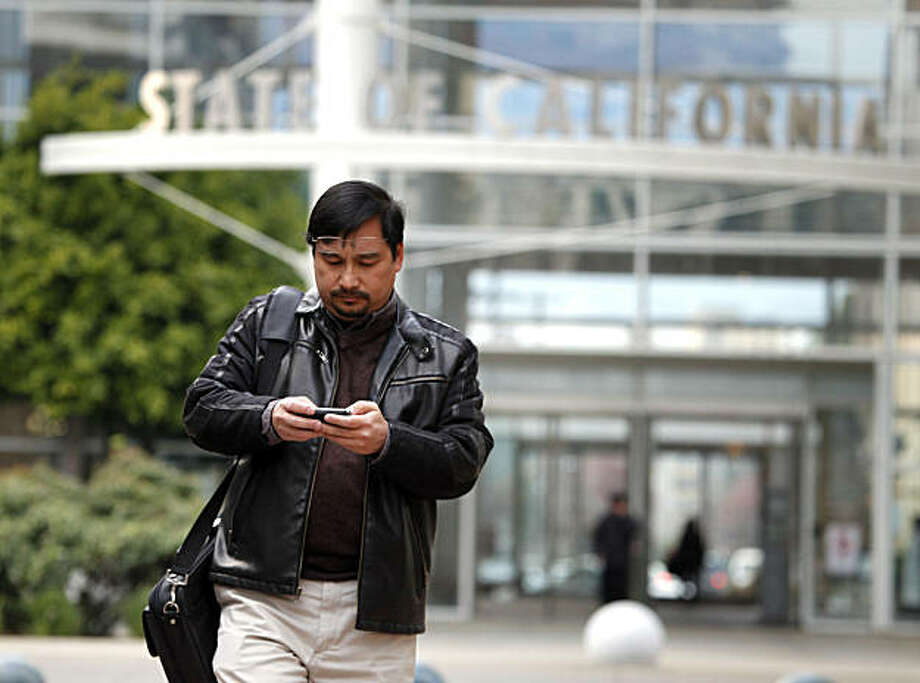 Dennis Espiritu a state employee exits the Elihu M. Harris building in Oakland Tuesday Jan 11, 2011 reading his office E-mails. Espiritu claims his state owned phone is the most efficient way of communication; not only the phone portion but also he gets text and E-Mails on his unit. Photo: Lance Iversen, The Chronicle
