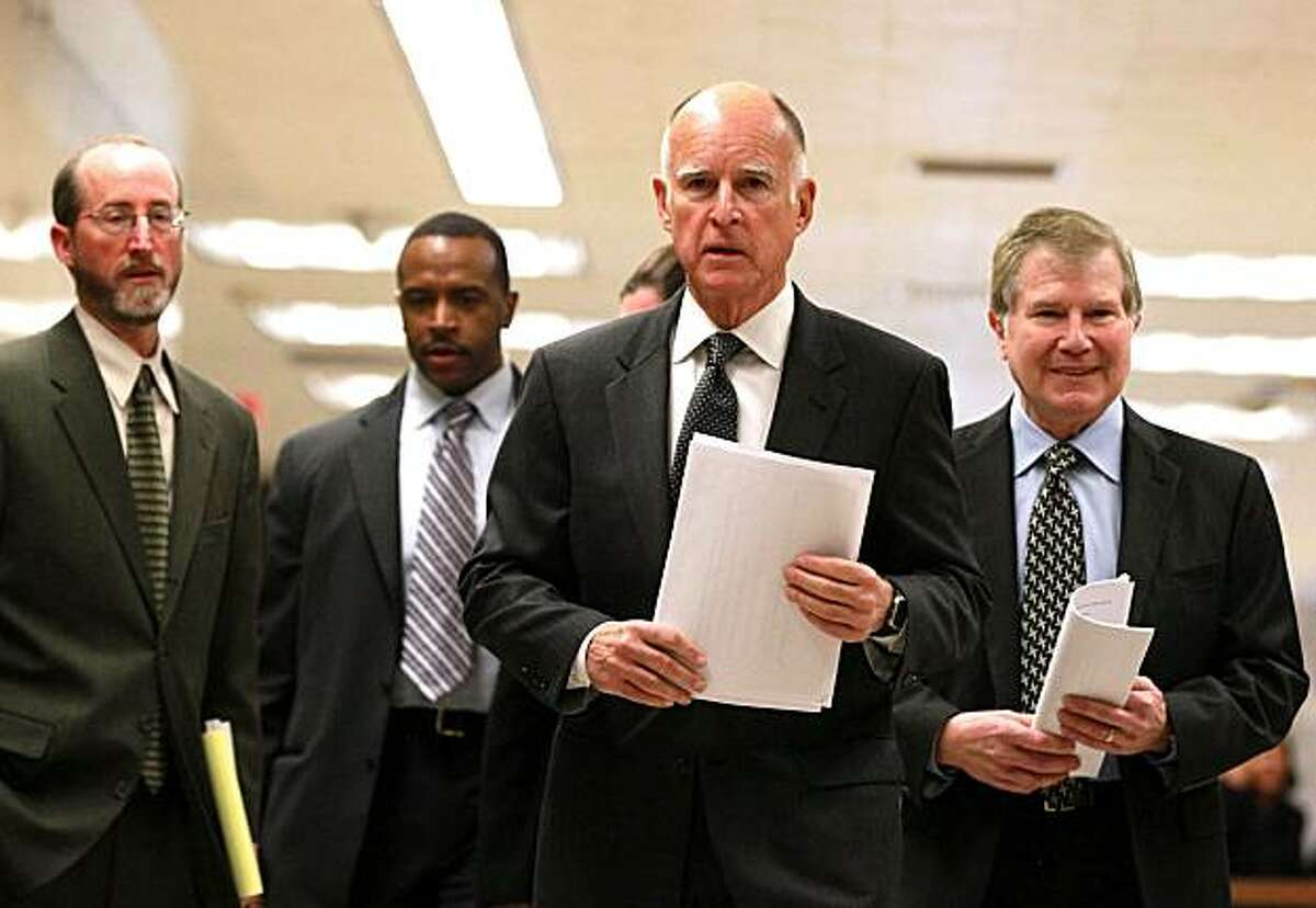 California Governor Jerry Brown (C) walks with advisors to a press conference about his proposed budget at the California State Capitol on January 10, 2011 in Sacramento, California. Governor Brown announced a balanced state budget that cuts spending by $12.5 billion and includes an eight to ten percent cut in take home pay for state employees and proposes a