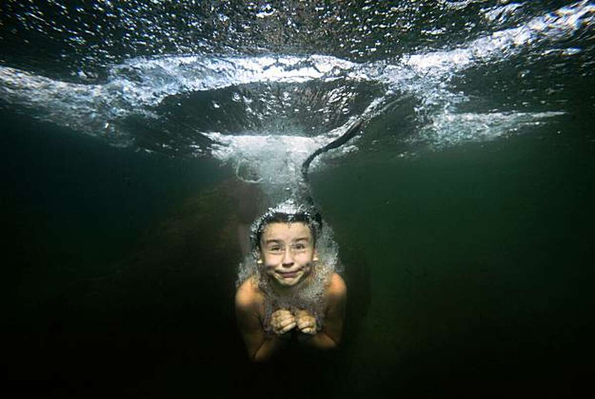 A girl dives in a lake 100 km (62 miles)west off St. Petersburg, Russia, Friday, Aug. 7, 2009. (AP Photo/Dmitry Lovetsky)