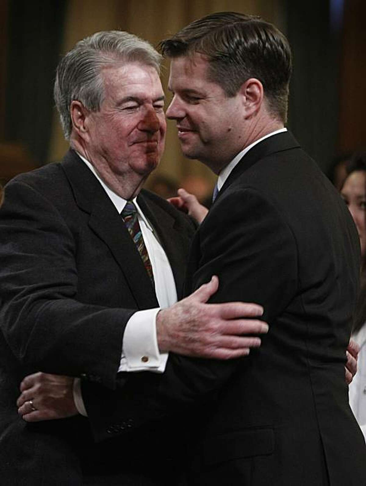 Mark Farrell (right) hugs his dad, John, after being sworn in as one of four new members on the Board of Supervisors at City Hall in San Francisco on Saturday.