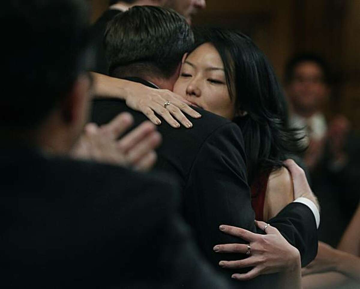 Jane Kim and Mark Farrell hug each other after being sworn in as new members of the Board of Supervisors at City Hall in San Francisco on Saturday.