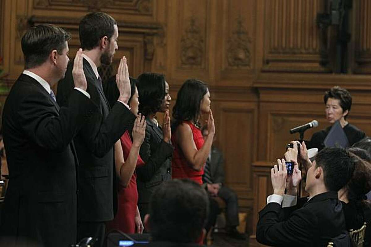 Family members snap photos as (from left) Mark Farrell, Scott Wiener, Jane Kim, Malia Cohen and incumbent Carmen Chu are sworn in by Judge Cynthia Lee (far right) to serve on the Board of Supervisors at City Hall in San Francisco on Saturday.