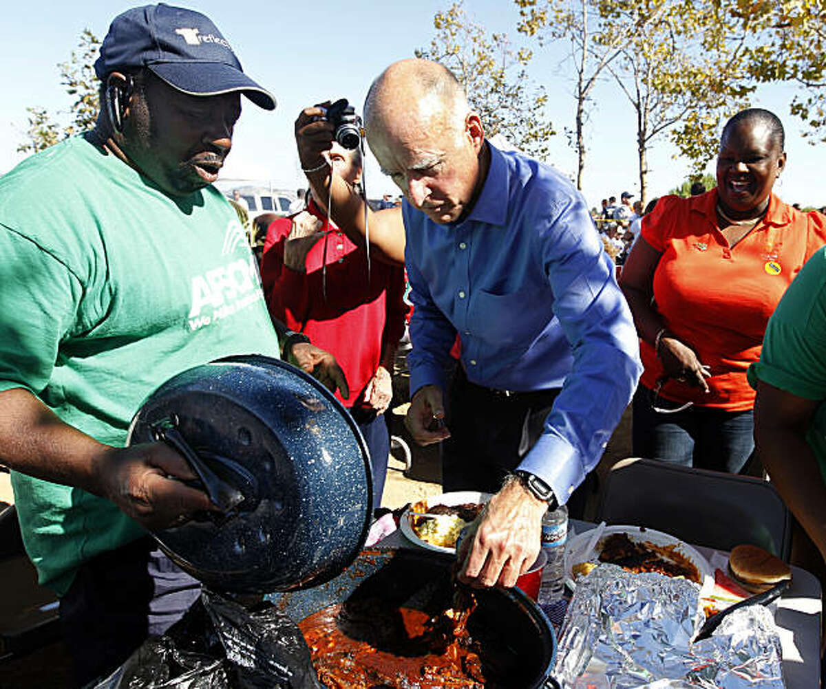 Democratic candidate for governor Jerry Brown samples BBQ food from supporter Morris Tatum (left) at the annual Alameda Labor Council picnic at Shoreline Park in Oakland, Calif. on Monday, Sept. 6, 2010.
