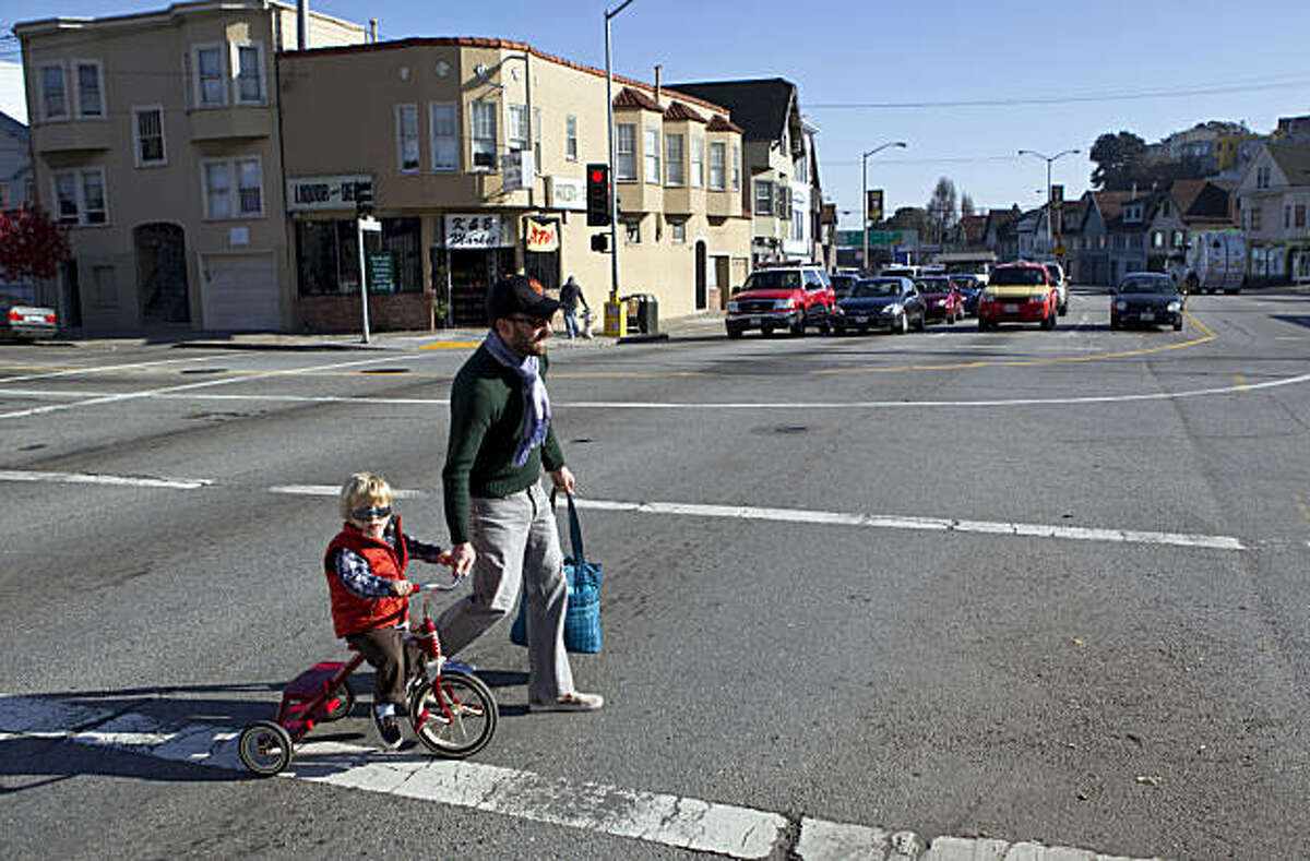Rob Thomson helps Leo Thomson, age 2, cross Cesar Chavez Street in San Francisco, Calif., on Thursday, January 6, 2011. The city has unveiled a plan to remake the street with fewer traffic lanes, a new pedestrian plaza and new medium plantings.