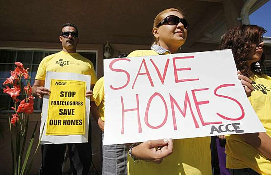 In this Sept. 24, 2010 photo, supporter Marisa Salas, right, holds a sign during a foreclosure and eviction rally at the home of Carlos Moreno in Menlo Park, Calif. Moreno has owned his home since 2006, had his home under foreclosure since January 2010, and was served eviction notice in July 2010. His case is now pending with the bank. For most Americans at risk of losing their homes, the brutal business of foreclosure goes on. Photo: Paul Sakuma, AP