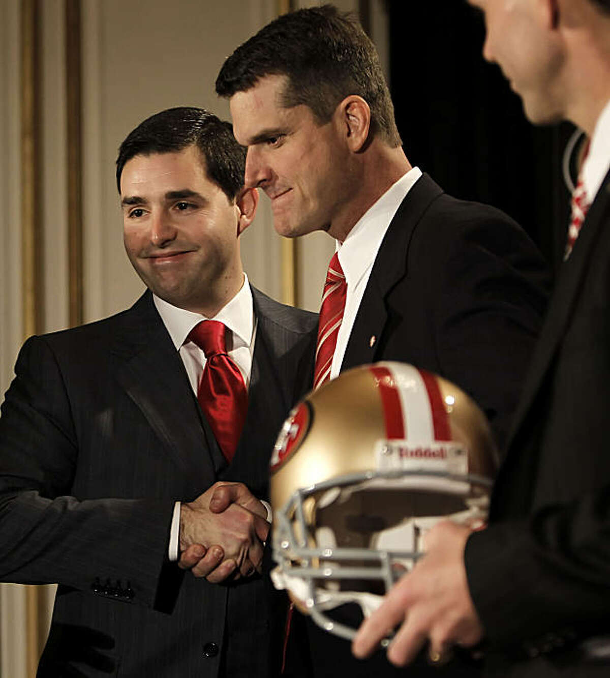 Jed York (left) shakes hands with the new head coach of the San Francisco 49ers, Jim Harbaugh, at a news conference in San Francisco on Friday.