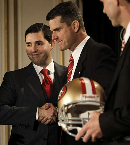 Jed York (left) shakes hands with the new head coach of the San Francisco 49ers, Jim Harbaugh, at a news conference in San Francisco on Friday. Photo: Michael Macor, The Chronicle