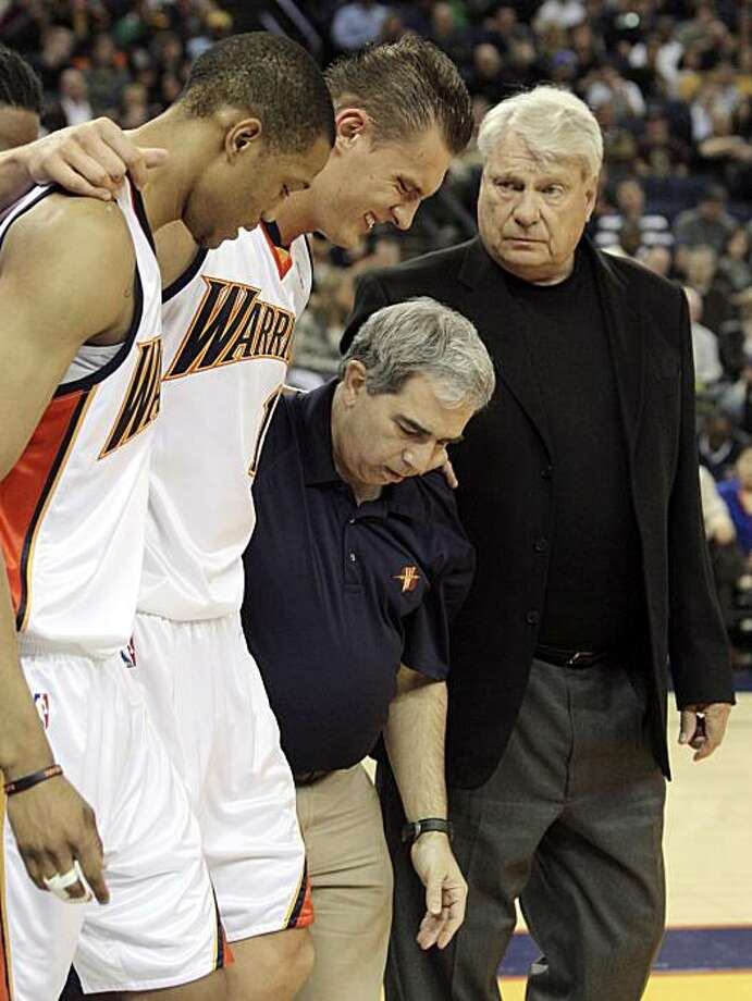 Golden State Warriors' Anthony Randolph, left, and head athletic trainer Tom Abdenour, third from left, assist Andris Biedrins, of Latvia, off the court as coach Don Nelson watches during the first half of an NBA basketball game against the Dallas Mavericks Friday, March 13, 2009, in Oakland, Calif. (AP Photo/Ben Margot) Photo: Ben Margot, AP