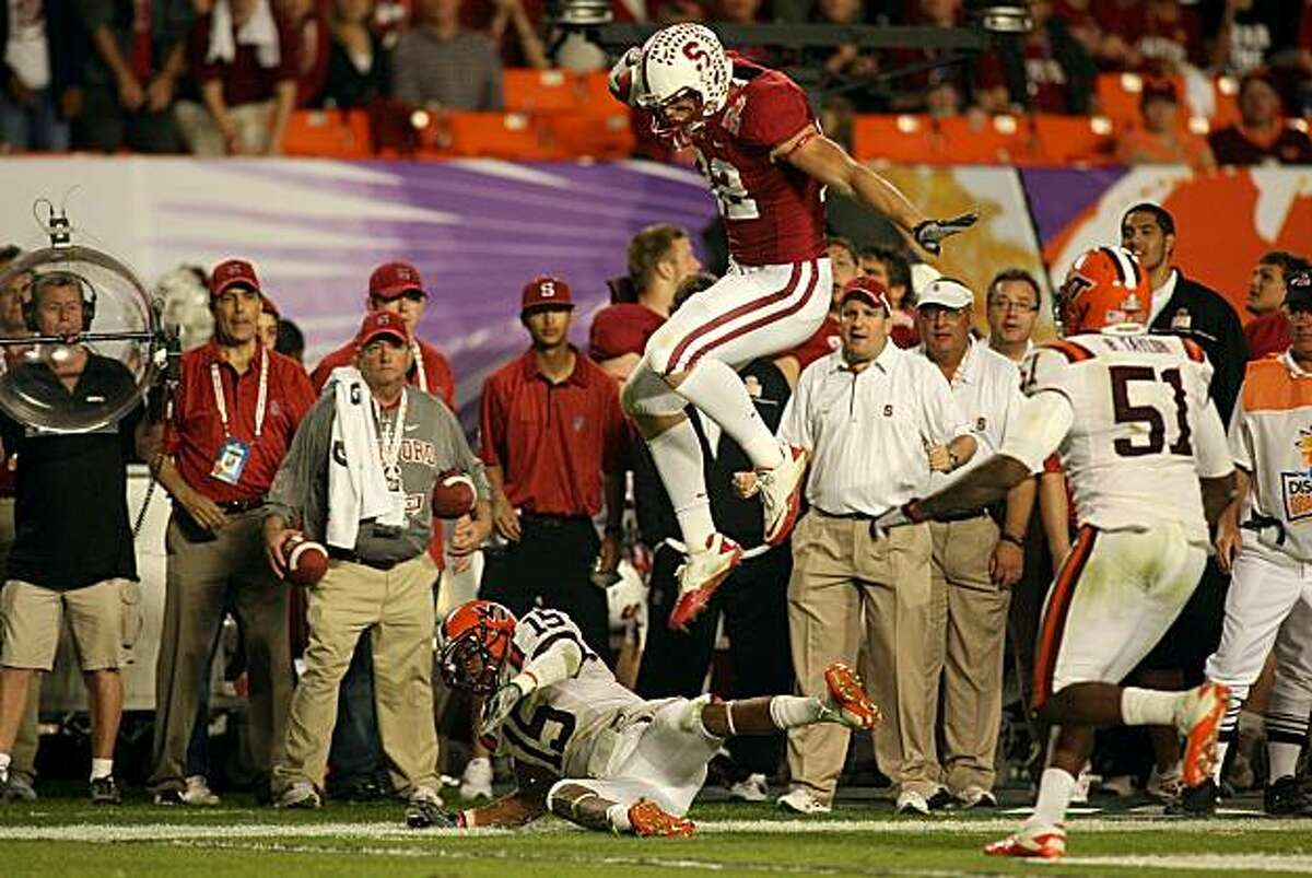 MIAMI, FL - JANUARY 03: Coby Fleener #82 of the Stanford Cardinal leaps over Eddie Whitley #15 of the Virginai Tech Hokies as he runs for yards after the catch during the 2011 Discover Orange Bowl at Sun Life Stadium on January 3, 2011 in Miami, Florida.