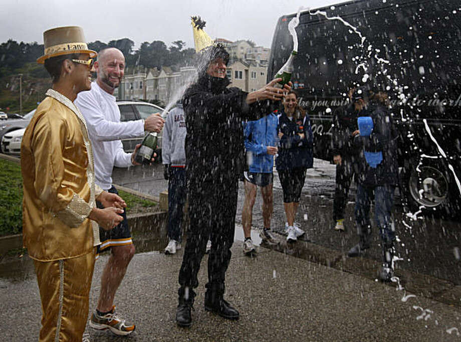 From left, Ryan Ung, Josh Muxen and George Ridgely spray Champagne as several runners complete a ceremonial race in San Francisco on Saturday to commemorate this year's 100th running of the Bay to Breakers. The New Year's Day run followed the original course of the inaugural race, known then as the Cross City Race. Photo: Paul Chinn, The Chronicle