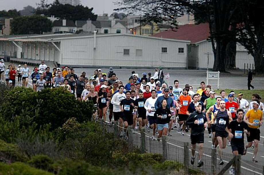 A group of runners heads past Crissy Field, then up a hill to the Golden Gate Bridge. More than 20,000 runners circled the city for the annual San Francisco Marathon Sunday July 26, 2009. Photo: Brant Ward, The Chronicle