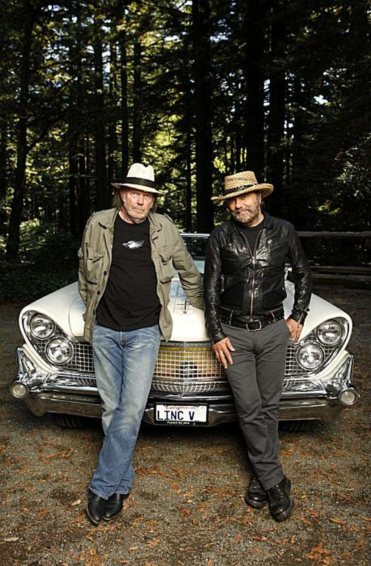 In this Sept. 10, 2010 file photo, musicians Neil Young, left, and Daniel Lanois are photographed beside Young's 1959 hybrid Lincoln Continental in Woodside, Calif. A fire at a San Francisco Bay area warehouse that stored memorabilia belonging toNeil Young started the vintage car the singer had converted into a hybrid vehicle. Belmont-San Carlos Fire Marshal Jim Palisi told the San Mateo County Times the Nov. 9 fire began in Young's 1959 Lincoln Continental and then spread to the nearby warehouse. Young had converted the car to run on electric batteries and a biodiesel-powered generator as part of the LincVolt project.