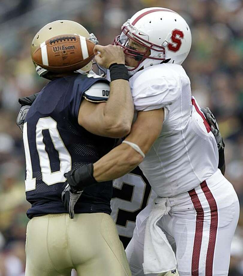 Stanford linebacker Shayne Skov, right, hits Notre Dame quarterback Dayne Crist to cause a fumble during first half of an NCAA college football game in South Bend, Ind., Saturday, Sept. 25, 2010. Stanford recovered the ball. Photo: Michael Conroy, AP