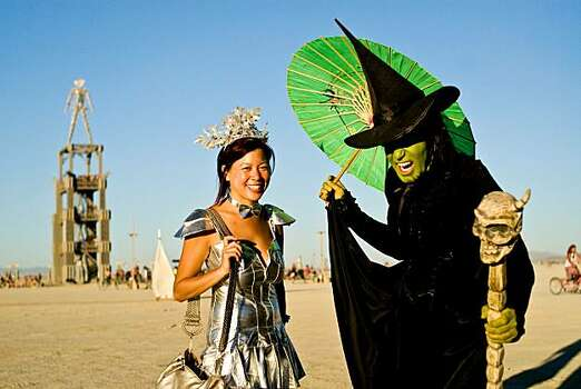 Burners show off their costumes as the man keeps watch in the distance during Burning Man 2010 in Black Rock City, Nev.  Photo: Vince Alonzo, AP