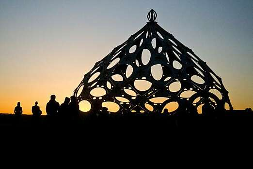 In this photo taken Sept. 2, 2010, burners greet the sun as it rises over Black Rock City, Nev. during Burning Man 2010. Photo: Vince Alonzo, AP