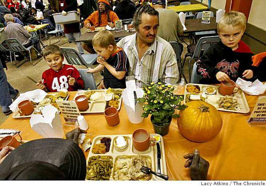 Jeffery Chambers sits with his sons, Jeffrey, Jr., left, Kyle, and Joshua, as they have Thanksgiving dinner at the St. Anthony Foundation dining room. Photo: Lacy Atkins, The Chronicle