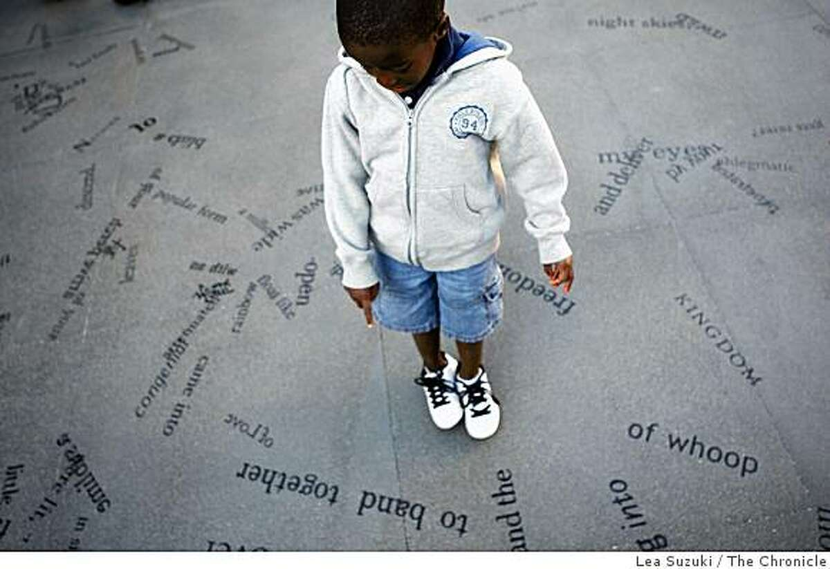 """Christian McDaniels, 5, of Albany points to the words as he spells out the letters on the corner of Broadway and Columbus Streets before the unveiling and dedication ceremony for """"Language of the Birds."""""""
