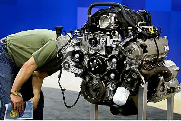 Martin Roger moves in for a close inspection of a Ford V8 engine at the 51st annual International Auto Show.