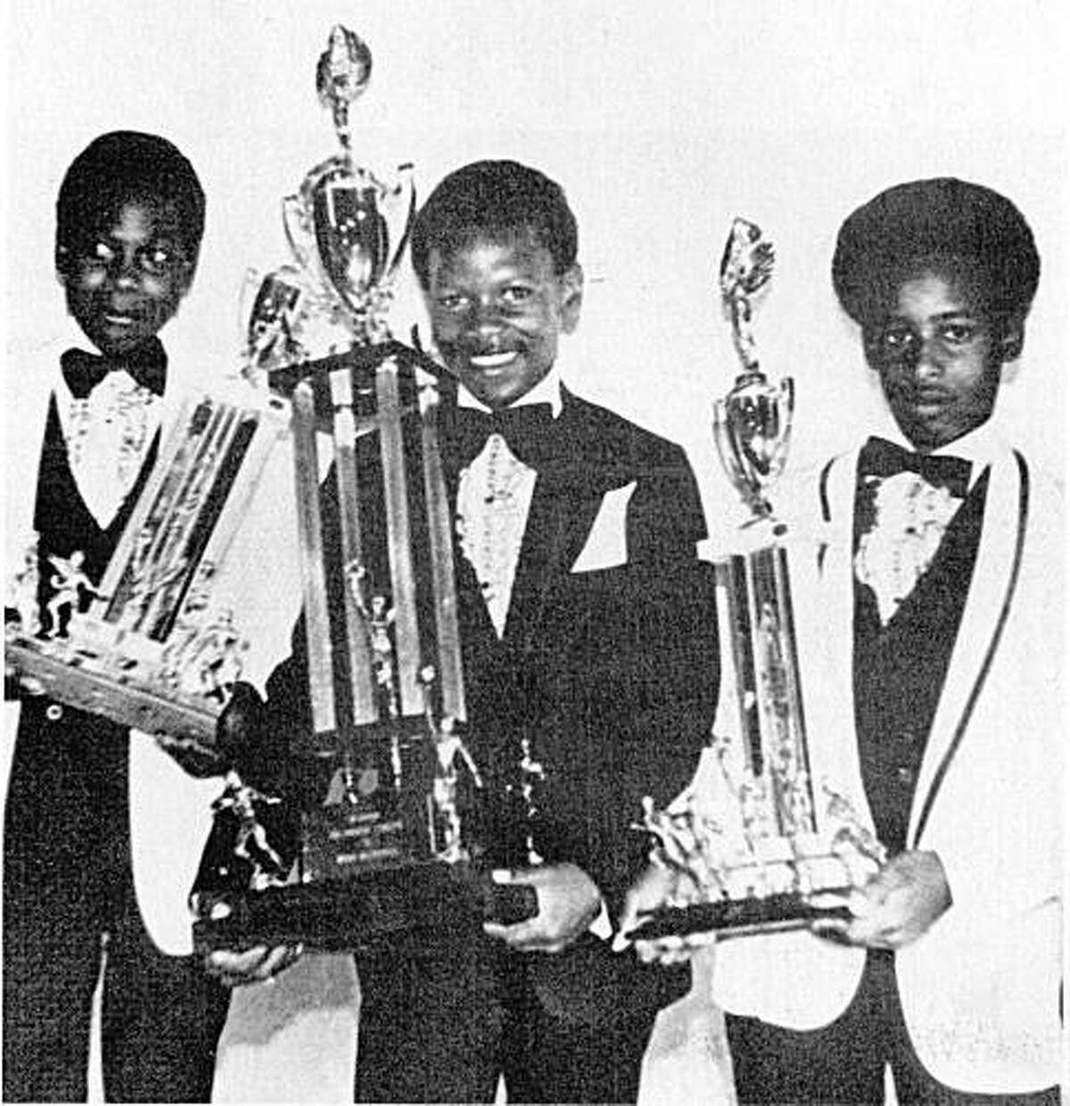 Rickey Henderson, Center, with trophy as athlete of the year at Bushrod Park. Kerry Bland is on left and right is Lamont Whitehead.