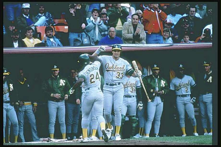 1989:  Outfielders Rickey Henderson and Jose Canseco of the Oakland Athletics celebrate during a playoff game against the San Francisco Giants at Candlestick Park in San Francisco, California.  Mandatory Credit: Otto Greule  /Allsport Photo: Otto Greule Jr, Getty Images