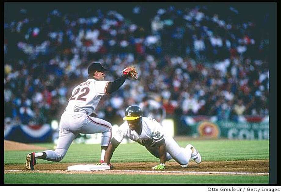 1989:  First baseman Will Clark of the San Francisco Giants tries to tag out outfielder Rickey Henderson of the Oakland Athletics during the World Series at the Oakland Coliseum in Oakland, California. Photo: Otto Greule Jr, Getty Images