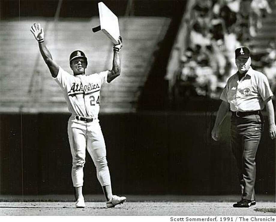 April 28, 1991 Rickey Henderson holds up 2nd base after he tied Lou Brock's record during an A's vs. Angels game at the Oakland Coliseum. The umpire at the right is Drew Coble. Photo: Scott Sommerdorf, The Chronicle