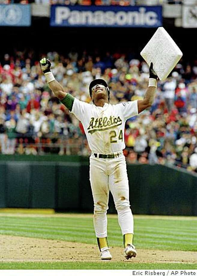 1991: Oakland Athletics' Rickey Henderson celebrates and raises third base after setting the all-time stolen base record during the Athletics' baseball game in Oakland, Calif., against the New York Yankees. The stolen base was Henderson's 939th, moving him past Lou Brock. Henderson was voted into baseball's Hall of Fame on Monday, Jan. 12, 2009. (AP Photo/Eric Risberg, File) Photo: Eric Risberg, AP Photo