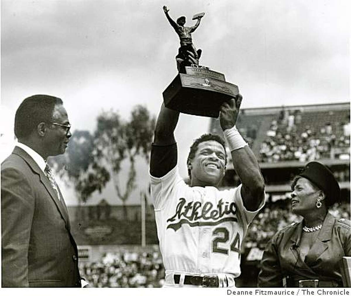 May 1, 1991 Rickey Henderson steals 3rd base at Oakland Coliseum against the N.Y. Yankees to surpass Lou Brock's previous record of 938 stolen bases. He raises the trophy he was presented with his Mother, Bobbie, at his right and Lou Brock at his left.