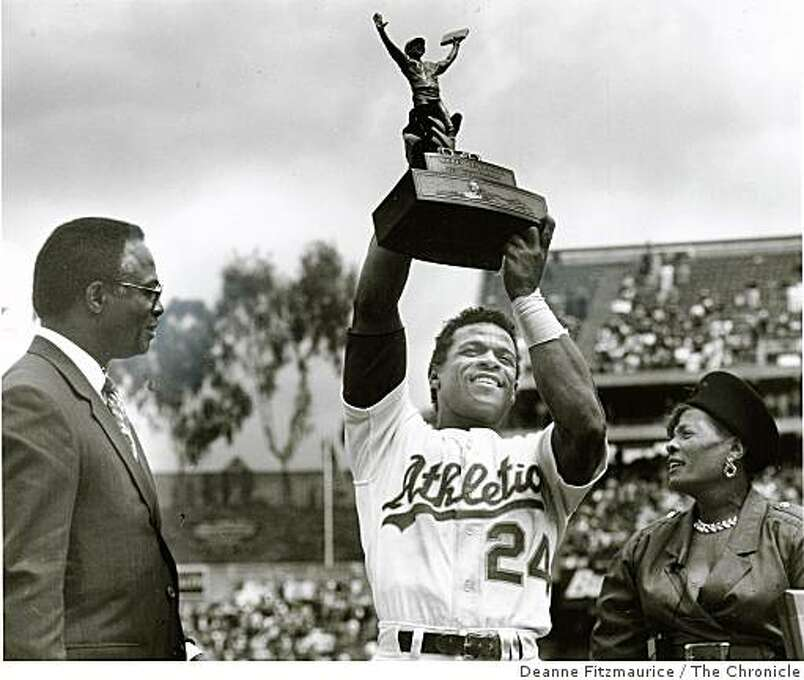 May 1, 1991 Rickey Henderson steals 3rd base at Oakland Coliseum against the N.Y. Yankees to surpass Lou Brock's previous record of 938 stolen bases. He raises the trophy he was presented with his Mother, Bobbie, at his right and Lou Brock at his left. Photo: Deanne Fitzmaurice, The Chronicle