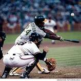 A's Rickey Henderson makes contact during game four of the 19989 World Series. KENNY is behind the plate for the Giants.