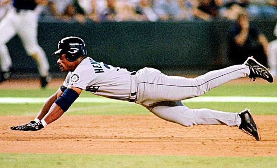 Seattle Mariners' Rickey Henderson dives for third base for a eighth inning triple against the Arizona Diamondbacks 16 July 2000 in Phoenix.  Photo: Mike Fiala, AFP/Getty Images